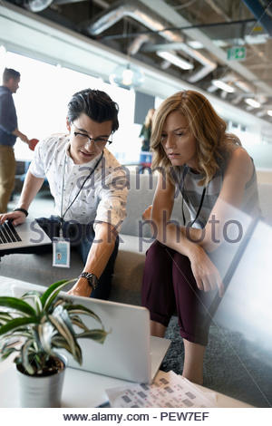 Businessman and businesswoman talking, using laptop in office lounge - Stock Photo
