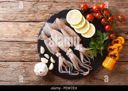 Fresh raw squid with tentacles closeup and vegetable ingredients on the table. horizontal top view from above - Stock Photo