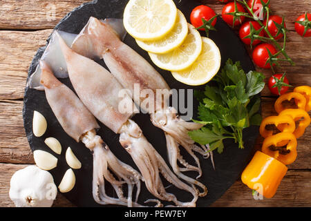 Seafood fresh squid with tentacles close-up and vegetable for cooking on the table. horizontal top view from above - Stock Photo
