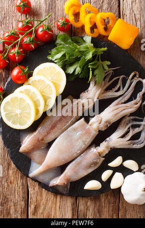 Seafood fresh squid with tentacles close-up and vegetable for cooking on the table. Vertical top view from above - Stock Photo
