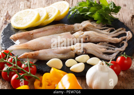 Fresh raw squid with tentacles closeup and vegetable ingredients on the table. horizontal - Stock Photo