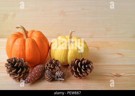 Vivid orange and yellow ripe pumpkins with many natural dry pine cones on the wooden table - Stock Photo