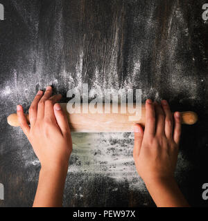 Girl hands keep rolling pin with flour on dark black table, baking background, top view, copy space for your text, meru, recipe. Square crop - Stock Photo
