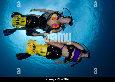 Two female divers (MR) on underwater scooters, Hawaii. - Stock Photo