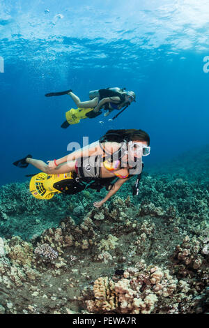 Two female divers (MR) on underwater scooters on off Maui, Hawaii. - Stock Photo