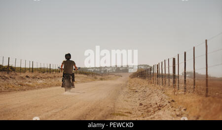 Rear view of man riding motor cycle on a country road. Motorcyclist rides along a countryside road. - Stock Photo