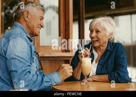 Portrait of cheerful senior couple sitting at table in cafe. Happy old couple talking and enjoying a cold coffee at cafe. - Stock Photo