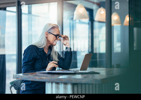 Senior business woman working on laptop in office. Caucasian mature female looking at laptop computer while sitting at her desk. - Stock Photo