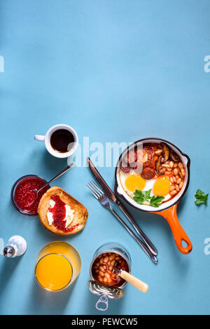 English Breakfast in cooking pan with fried eggs, sausages, beans, toasts and coffee on concrete table, copy space - Stock Photo