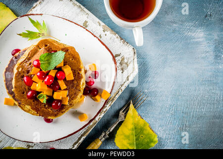 Autumnal breakfast idea, pumpkin pancakes, with slices of pumpkin, maple syrup or honey, cranberry, on a blue concrete background, space for text - Stock Photo