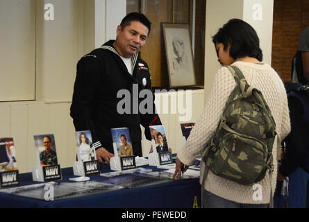 OLD WESTBURY, N.Y. (Feb. 1, 2016) Operations Specialist 2nd Class Manuel Castillo, assigned to Navy Recruiting District New York, talks with a student during a visit of Westbury High School in Long Island. (U.S. Navy photo by Chief Mass Communication Specialist Travis Simmons/Released) - Stock Photo