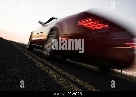 A low angle blurred view of a convertible sports car silhouetted  on the road at sunset. - Stock Photo