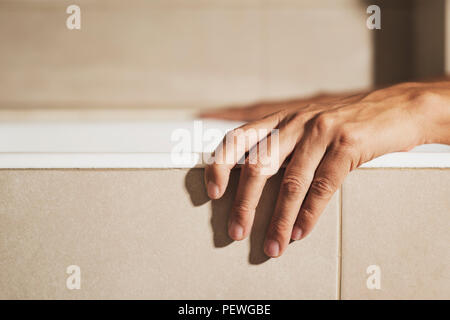 closeup of the hand of a young caucasian man on the side of a white bathtub while is taking a bath, in a beige bathroom - Stock Photo