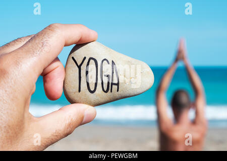 closeup of the hand of a young caucasian man on the beach holding a stone with the yoga written in it, and a young caucasian man practicing yoga in th - Stock Photo