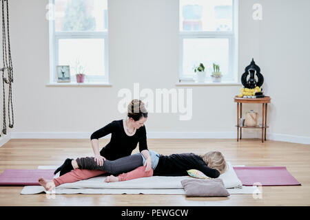 Woman receiving a Thai massage from a practioner. - Stock Photo