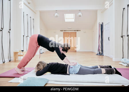 Woman lying on her front, receiving a Thai massage from a masseur leaning over with hands on her back. - Stock Photo