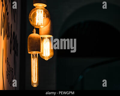 Different types of vintage glowing light bulbs on black. Edison lamps - Stock Photo