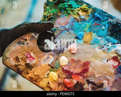 Wooden art palette with oil paints. Mixing colors together. Artistic instrument with many colors. Working tool with squeezed out tubes of paint. - Stock Photo