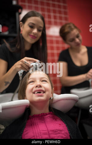 Hairdressers with little girls, washing hair in sink - Stock Photo