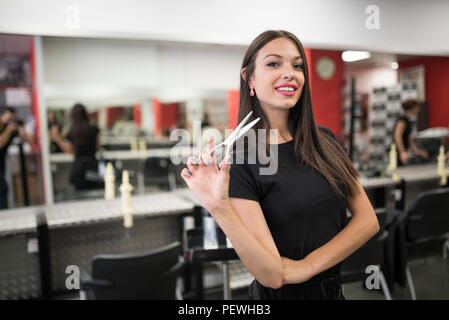 Hairdressers with scissors posing in salon smiling - Stock Photo