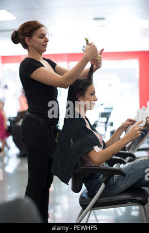 Hairdresser cuts and comb young womans hair - Stock Photo