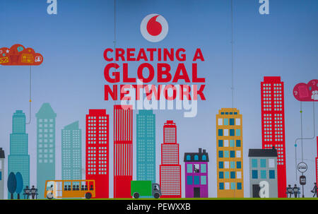 Vodafone logo advertising a global network on an advertising hoarding, or advertising board. - Stock Photo