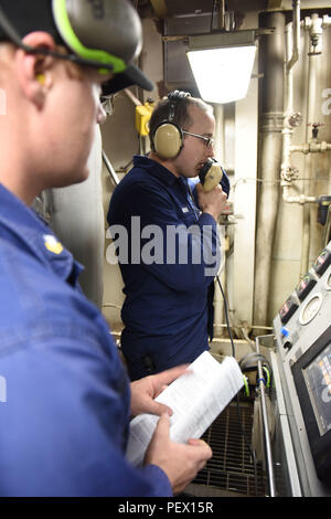Fireman Joseph Guenther, a member of the Coast Guard Cutter Polar Star's main propulsion division, relays a message to the cutter's engineering control central while Petty Officer 2nd Class Keith Bryan, a machinery technician in the Polar Star's main propulsion division, observes during engineering casualty exercises in the Ross Sea, near Antarctica, Feb. 4, 2016. The drills simulate emergency situations in engine spaces for the ship's engineers to learn and apply their initial response techniques. (U.S. Coast Guard photo by Petty Officer 2nd Class Grant DeVuyst) - Stock Photo