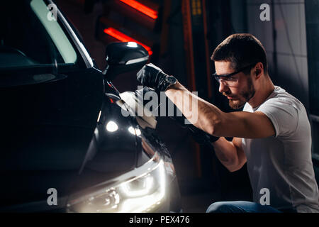 Car detailing - Hands with orbital polisher in auto repair shop. Selective focus. - Stock Photo