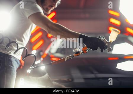 man wear protective mask and eyewear at work. Automobile industry. Car wash and coating business with ceramic coating polishing. Spraying varnish to c - Stock Photo