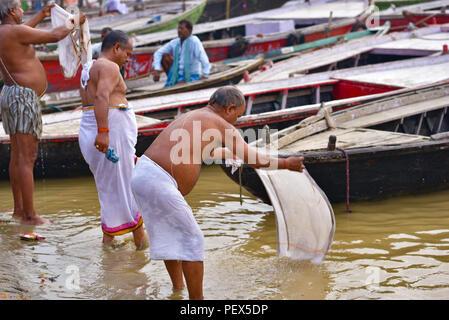 Hindu Indian pilgrims bathing and praying in Ganges river - Stock Photo