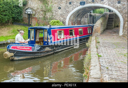 Narrowboat coming under bridge on the Staffordshire and Worcerstershire Canal - Stock Photo