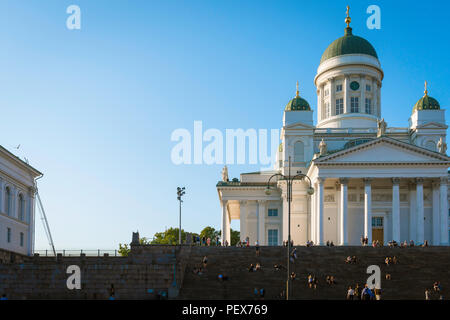 Finland tourism summer, view at sunset of the Lutheran Cathedral in Helsinki with tourists sitting on or ascending the grand staircase to its entrance. - Stock Photo