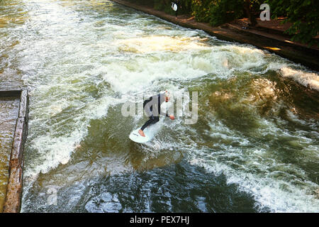 MUNICH, GERMANY - JULY 24, 2018 -  Munich, surfer riding the artificial wave on the Eisbach, small river across the Englischer Garten, in a summer mor - Stock Photo