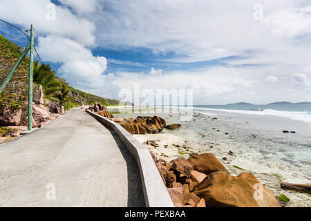 Low water at the remote east coast of La Digue, Seychelles with the only road in the foreground - Stock Photo
