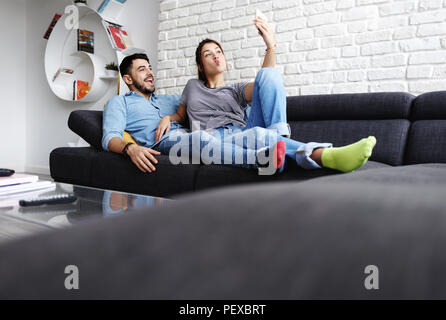 Young Couple Taking Selfie On Sofa At Home - Stock Photo