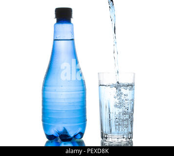 Blue water bottle isolated on white background with small water droplets and a clear drinking glass being filled - Stock Photo