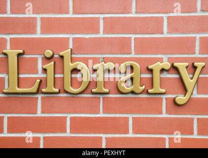 Letters spelling OFFICE sign in gold on a brick wall Stock