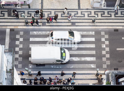 Lisbon, Portugal - March 11, 2016: A van and a car drive over a zebra striped pedestrian crossing in the Baixa neighbourhood of central Lisbon, viewed - Stock Photo