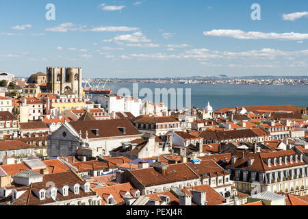 The Se de Lisboa cathedral stands out in the cityscape of rooftops of Lisbon, with the Tagus River estuary behind, viewed from the Elevador de Santa J - Stock Photo