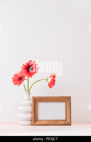 White landscape frame mock up with a vase of gerbera beside the frame, overlay your quote, promotion, headline, or design, great for small businesses, - Stock Photo