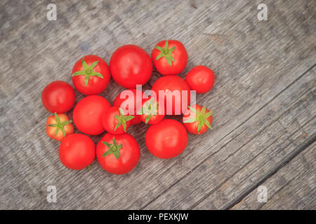 Cherry tomatoes on a wooden background. Autumn harvesting. Homemade vegetables.