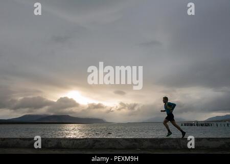 Man running along coastline, Puerto Natales, Magallanes Region, Chile - Stock Photo