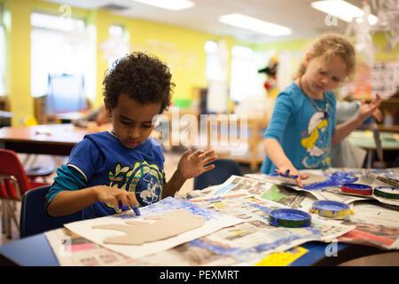 Schoolchildren finger painting in classroom - Stock Photo