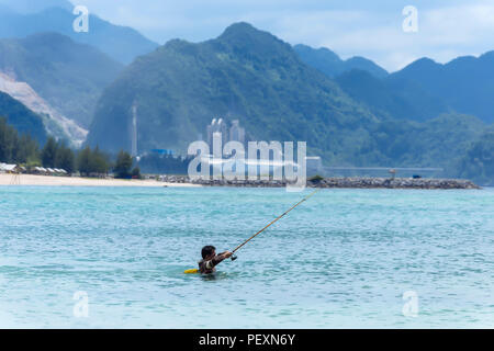 Fisherman in sea with fishing rod, Banda Aceh, Sumatra, Indonesia - Stock Photo