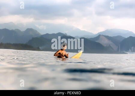 Young surfer in sea - Stock Photo