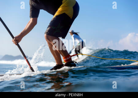 Two people paddle surfing in sea - Stock Photo