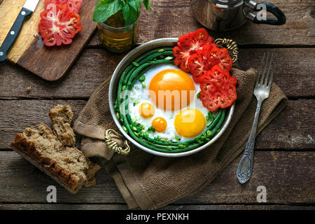 Sunny side fried eggs in a copper pan with tomatoes and green beans, copy space. - Stock Photo