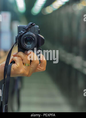 handheld shooting with a mirrorless camera - Stock Photo