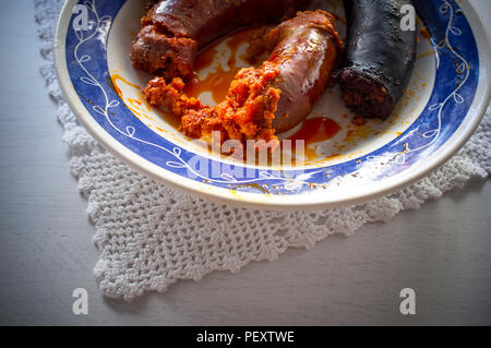 Red chorizo and black sausage morcilla just boiled on a plate over knitting cloth. Closeup - Stock Photo