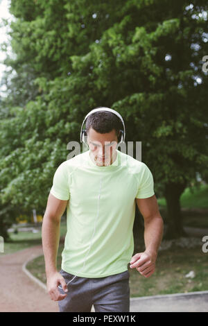 Young handsome man jogging in a park and listening to music. - Stock Photo